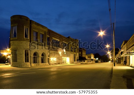 Night scene of small old town with street lights and dark blue sky - stock photo