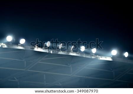 Night scene shot with sport arena floodlights seen through fog - stock photo