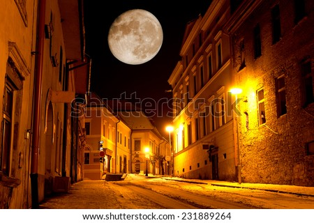 Night scene with big moon in old city - stock photo
