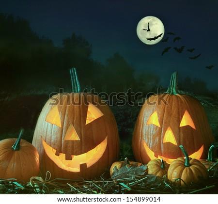Night scene with Halloween pumpkins and moon - stock photo