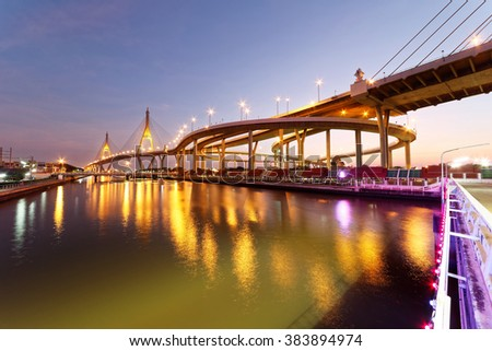 Night scenery of beautiful Bhumibol suspension bridge in Bangkok City Thailand, also known as the Industrial Ring Road Bridge ~ A landmark bridge over Chao Phraya River with reflections on the water - stock photo