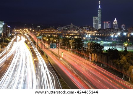 Night scenery of Taipei City, with Taipei 101 in XinYi District, downtown area with arch bridges and car trails on Dike Avenue ~ Romantic cityscape of Taipei at dusk by riverside (long exposure) - stock photo