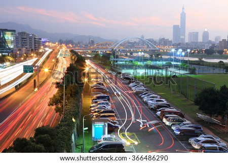 Night scenery of Taipei City with view of skyscrapers in downtown area, arch Bridges over Keelung River and busy car trails on Riverside Avenue during rush hour ~ Romantic cityscape of Taipei at dusk - stock photo
