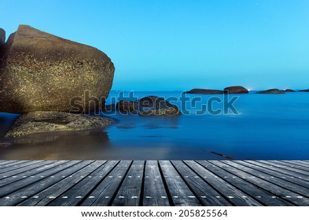Night sea and reefs, as well as the seaside wooden platform. - stock photo