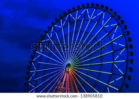 night shot of ferris wheel with light decoration against the dark blue sky