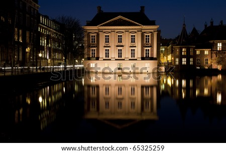 Night shot of museum Mauritshuis, next to the tower of power of Dutch politics, being the historical buildings situated next to a lake, called the Hofvijver, in the center of The Hague, Netherlands