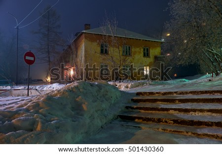 Night shot of street under snow with old residential house in winter season. Novosibirsk, Siberia, Russia