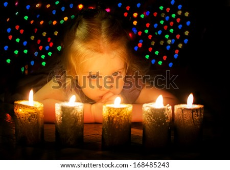 Night shot of the baby girl with candles with beautiful bokeh at background
