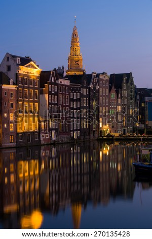 Night shot of traditional quaint houses in Amsterdam, capital of Holland, Netherlands,  with reflections in the canal at dusk, with church tower illuminated against dark blue sky - stock photo