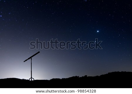 Night shot with a silhouette of a telescope, with a sky full of stars and the conjunction of Venus and Jupiter - stock photo