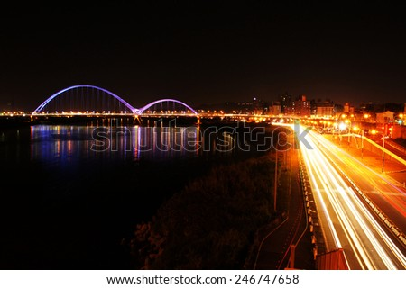Night sight view, bridge with rainbow color light at night and car light - stock photo