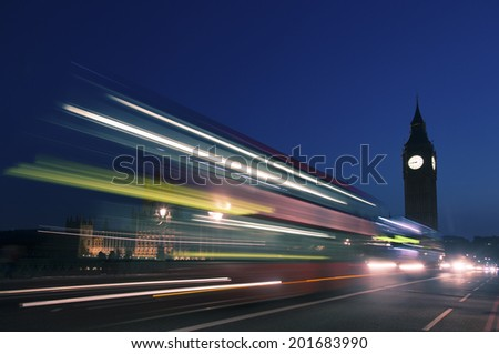 Night silhouette of Big Ben and light trail of a bus in front.