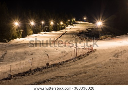 Night skiing on a snowy night with lights, two separated ski slopes and infrastructure at night - stock photo