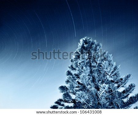 Night sky of falling shooting stars, dark space natural background, slow starry motion, winter Christmas time, tree forest with light lines, snowy landscape and star trails, rotation of planet Earth