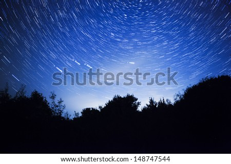 night sky, star trails and the forest - stock photo
