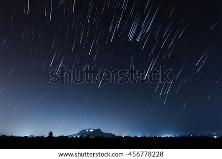 night sky, star trails and the mountain with long exposure stacking, soft focus - stock photo