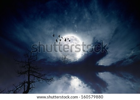 Night sky with full moon, flock of flying ravens, crows, old tree; reflection in water. Elements of this image furnished by NASA - stock photo
