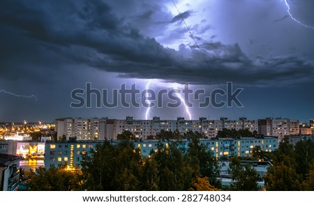 night thunderstorm over the buildings in the city - stock photo
