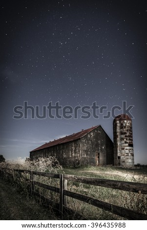 Night time image of an old farm barn and a country road in moonlight - stock photo