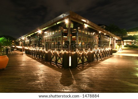 Night time on a veranda at a lake-side bar at a Kuala Lumpur resort hotel - stock photo