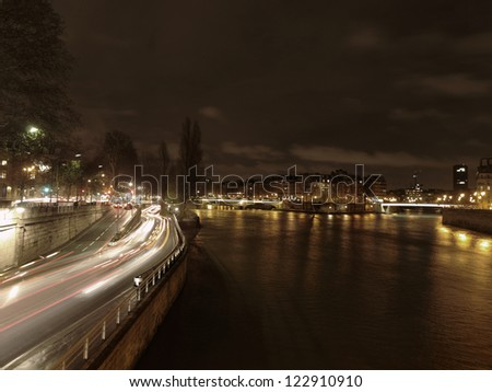 Night traffic along the river Seine in Paris, capital of France, with car lights in motion blur.
