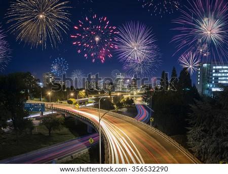 Night traffic in Portland, Oregon, USA with flashing fireworks Celebrating New Years Eve - stock photo