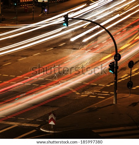 night traffic in the city with green traffic lights and light trails - stock photo