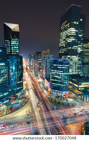 Night traffic speeds through an intersection in the Gangnam district of Seoul. - stock photo