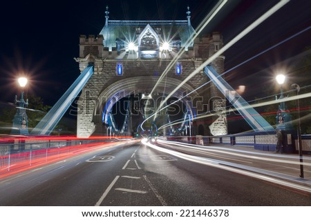 Night traffic through Tower bridge - stock photo