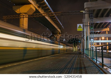 Night train station in the city and a passing train - stock photo