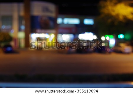 Night urban scene with blurred lights and the shopping center car park for use as a background. - stock photo