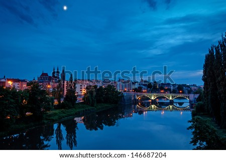 night vieew of St. Bartholomew Gothic Cathedral and old bridge over Elbe river in Kolin, Czech Republic  - stock photo
