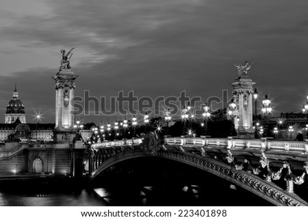 NIght view in black and white on the famous landmark Alexander iii bridge in Paris, capital of France, with beautiful characteristic street lights lighting the bridge and the dome of les invalides - stock photo