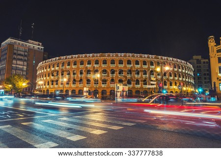 Night view of a Bullring Arena in Valencia, Spain. Car traffic lighting trail, motion blurred people. Dark sky. - stock photo
