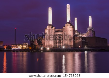 Night view of abandoned Battersea power station across river Thames, London, UK  - stock photo