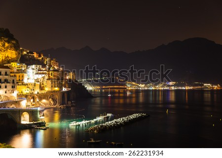 Night view of Amalfi on coast line of mediterranean sea, Italy, with colorful lights from the town and the dock, and the silhouette of the mountains in the background - stock photo