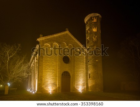 night view of ancient brick walls of an old Catholic church with one of the oldest  belltowers in Italy