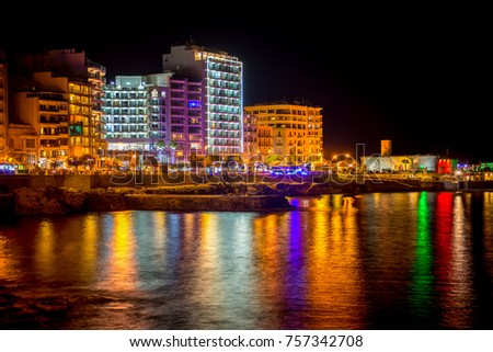 night view of beautiful european city Sliema with seafront and reflection in water, Malta