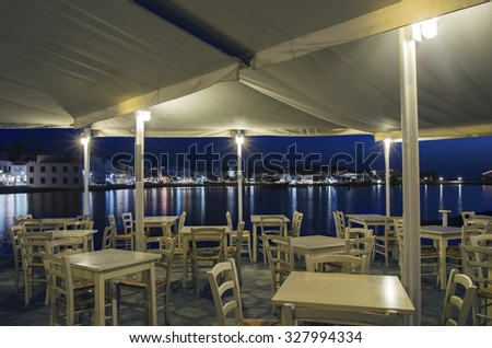 Night view of Chora and the port in Mykonos, Greece. Hora town cityscape lights reflected on the sea,through greek island restaurant with white wooden chairs and tables.A colourful,beautiful seascape. - stock photo