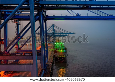 Night view of container terminal with gantry cranes container ship - stock photo