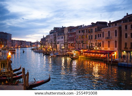 Night view of Grand Canal from Rialto bridge with gondolas in Venice. Italy