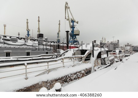 Night view of harbor cranes on the waterfront of the port covered with snow. Abandoned ships moored at the berth - stock photo