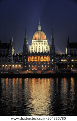 Night view of Hungarian parliament & Danube river, in Budapest Hungary. It is seat of the National Assembly of Hungary, one of Europe's oldest legislative buildings, a notable landmark of Hungary - stock photo
