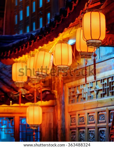 Night view of row of traditional oriental Chinese red street lanterns on carved facade of wooden house in the Old Town of Lijiang, Yunnan province, China. Focus on the first lantern. - stock photo