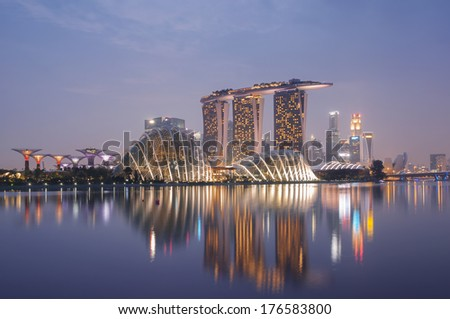 Night view of Singapore skyline, including:Gardens by the Bay, Supertree Grove, Cloud Forest, Flower Dome, Marina Bay Sands and the  Art Science Museum. - stock photo