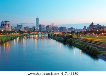 Night view of Taipei City by riverside with skyscrapers and beautiful reflections on smooth water ~ Landmarks of Taipei 101 Tower, Keelung River, Xinyi District and downtown area at dusk
