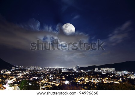 Night view of the brightly lit skyline of Georgetown city in Penang, Malaysia, with a full moon. - stock photo