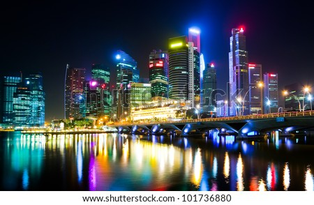 Night view of the city, with artificial light, reflecting on the water surface (Singapore) - stock photo
