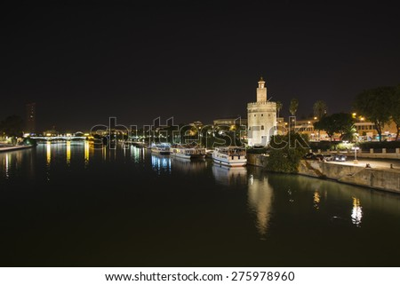 Night view of the Guadalquivir river in Seville, Spain. Gold Tower. Triana Bridge in the background. - stock photo
