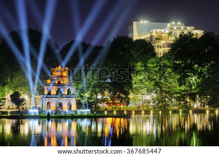 Night view of the Hoan Kiem Lake (Lake of the Returned Sword) and the Turtle Tower among blue light rays at historic centre of Hanoi in Vietnam. The Hoan Kiem Lake is a popular tourist destination.
